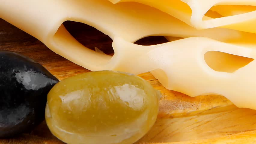 gold swiss cheese sliced on wooden platter with olives and tomato 1920x1080 intro motion slow hidef hd