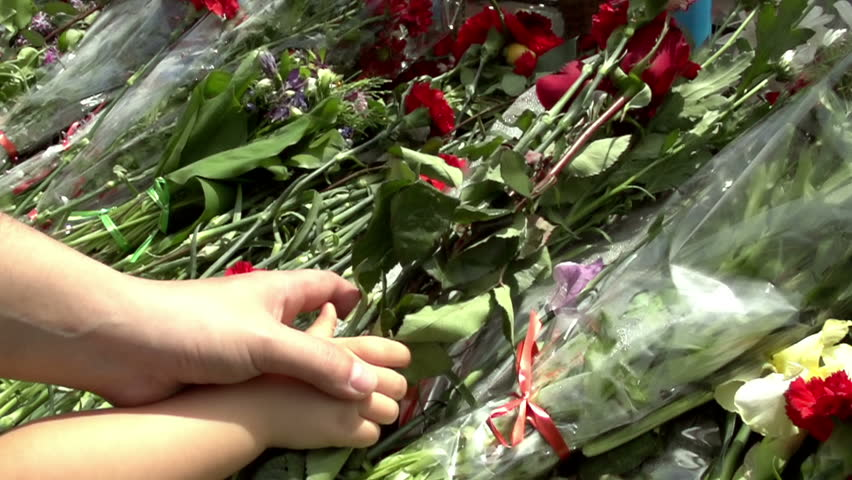 Placing Flowers. Hand adult helps the child to put flowers on memorial. Slow Motion at a rate of 480 fps | Shutterstock HD Video #3942881