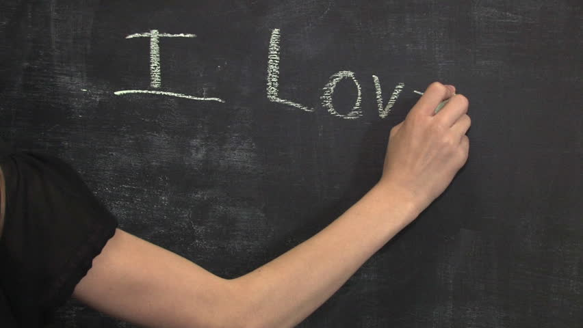 A child writes I Love Mommy on the chalkboard.