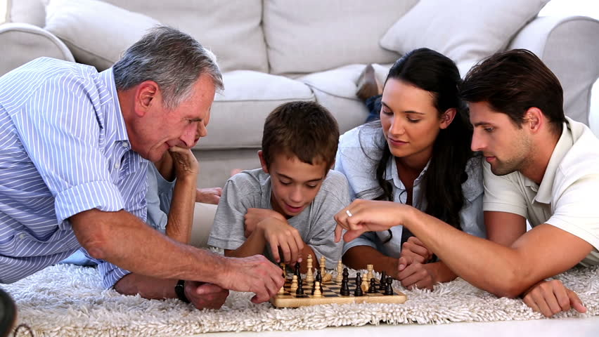 Extended family playing chess at home on the living room floor