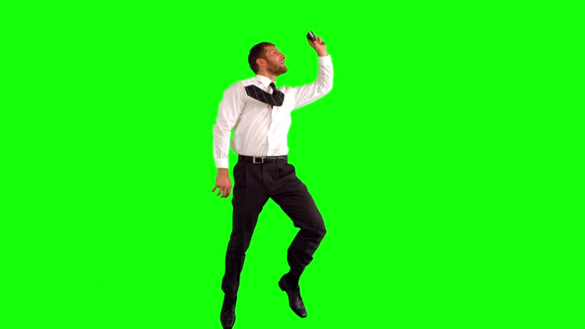 Businessman taking self portrait while leaping on green screen in slow motion #3989611