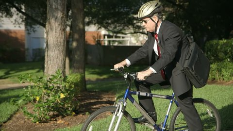 A businessman going green reduces his carbon footprint by riding a bike to work instead of driving the car.