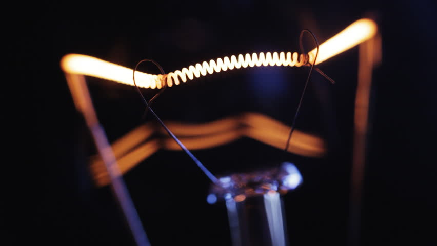 Incandescence thread, close up. Real light bulb turning on, flickering and turning off. Macro.