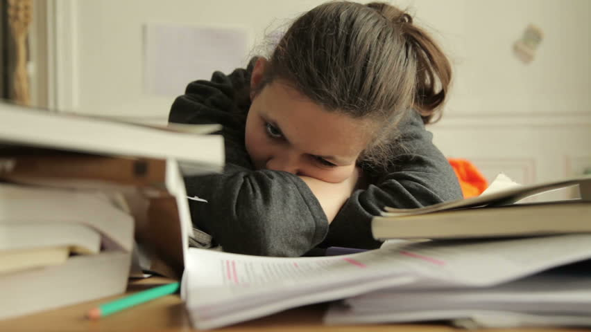 Female student looking tired of studies. Around her are piles of books and papers | Shutterstock HD Video #4032541