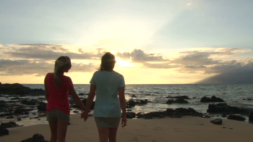 Two model released women walking together, holding hands on beach at ocean sunset.