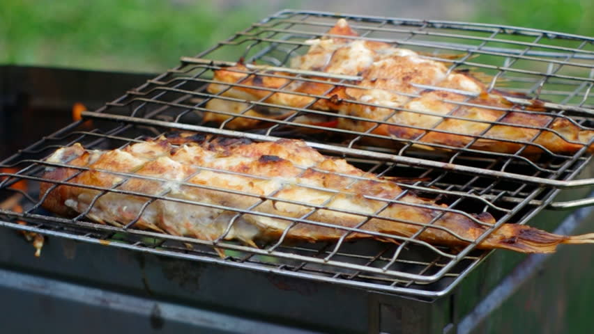 Barbecue .Rock Fish on the grill with flames . grilling sea fishes on campfire grate | Shutterstock HD Video #4058251