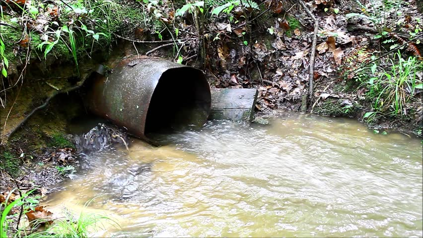 A waste water drainage pipe re-routing the water flow and polluting the environment at the same time as well as causing soil erosion