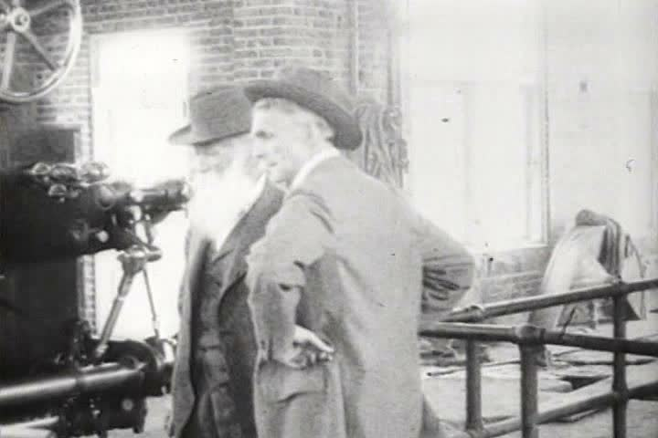 1920s - Henry Ford and John Burroughs work on an early steam engine in a factory and Burroughs cuts down a tree.