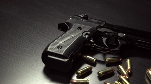 Dolly shot of 9 mm handgun with bullets