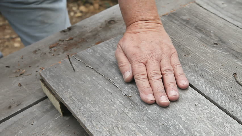 closeup of a man hammering a used nail into old boards