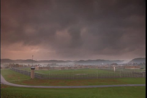 Wide, high angle view of the maximum security southern ohio correctional  facility, with morning mist over mountains, and dark cloudy skyin  lucasville, ohio