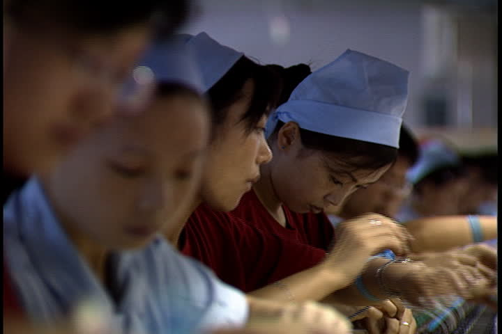 HUIZHOU, CHINA - SEPTEMBER 13, 2004: Row of seated factory workers adding elements to circuit boards.