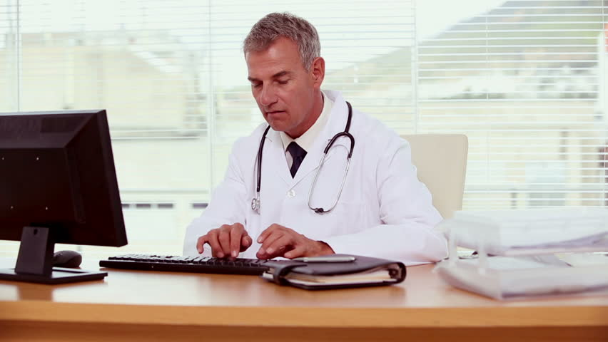 Smiling doctor using and typing on his computer | Shutterstock HD Video #4110181