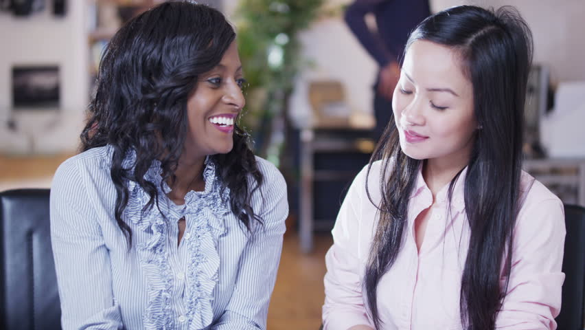 Two beautiful multi-ethnic businesswomen sitting in a light and modern open plan office and looking at a map of the world. They are discussing possibilities for future business ventures.  | Shutterstock HD Video #4130371