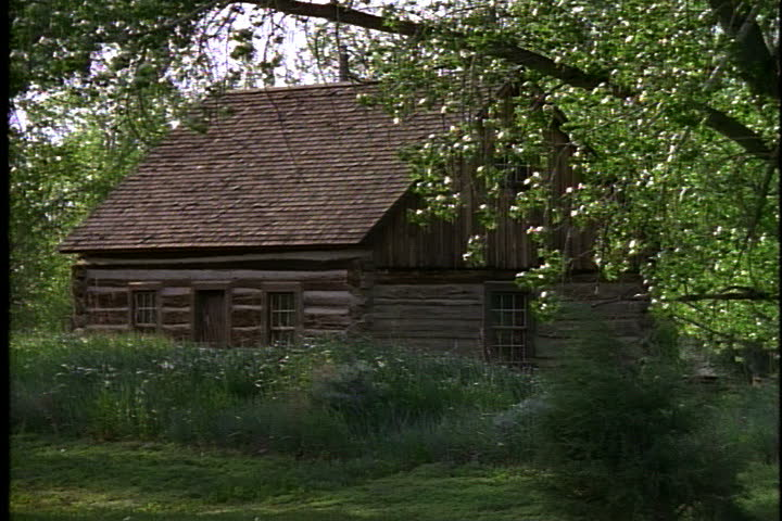 Exterior of Teddy Roosevelt's log cabin, surrounded by green grass and trees in Medora, North Dakota.