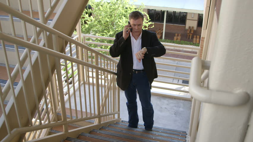 A mature handsome businessman using a cell phone walks up the steps of an outside stairwell then stops and talks.