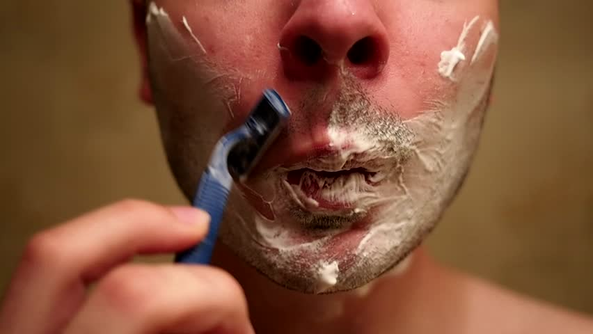 Man shaves his moustache, that has shaving cream on it, in front of mirror.