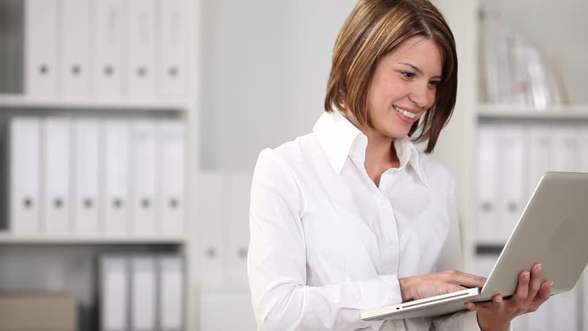 Happy woman working on a laptop in the office and smiling