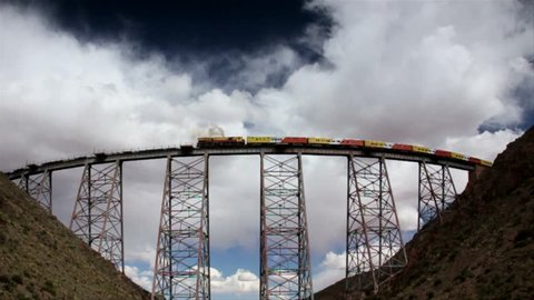 """Train of the Clouds. Tren a las Nubes, Argentina. Viaduct """"La Polvorilla"""" seen from below while the train is passing through blowing and sounding the siren. Cumulonimbus in the sky."""