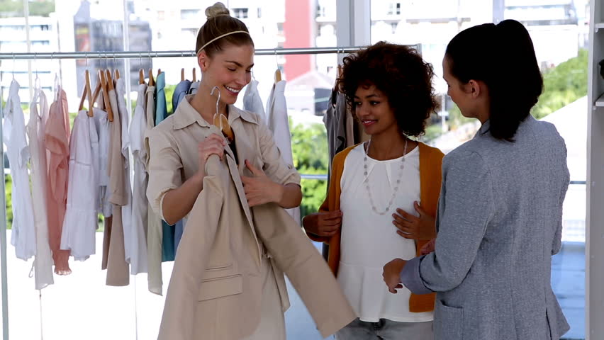 Pretty woman trying a jacket with friends in a clothing store