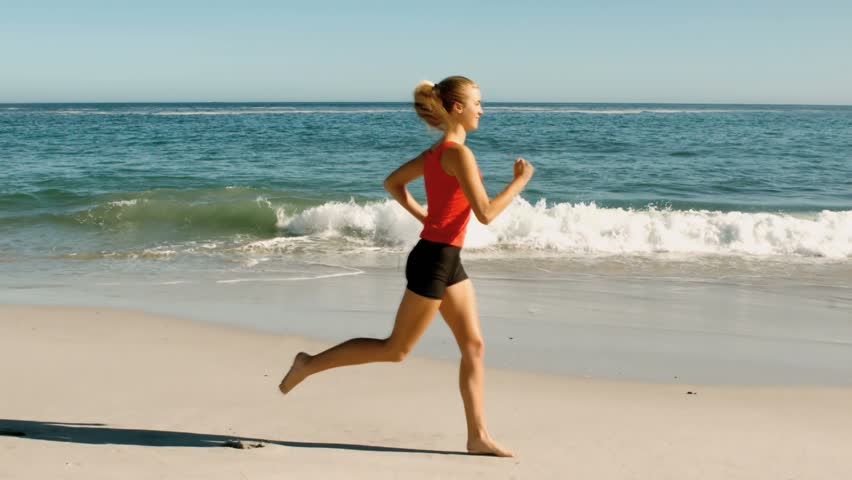 Woman with red tank top running on the beach in slow motion