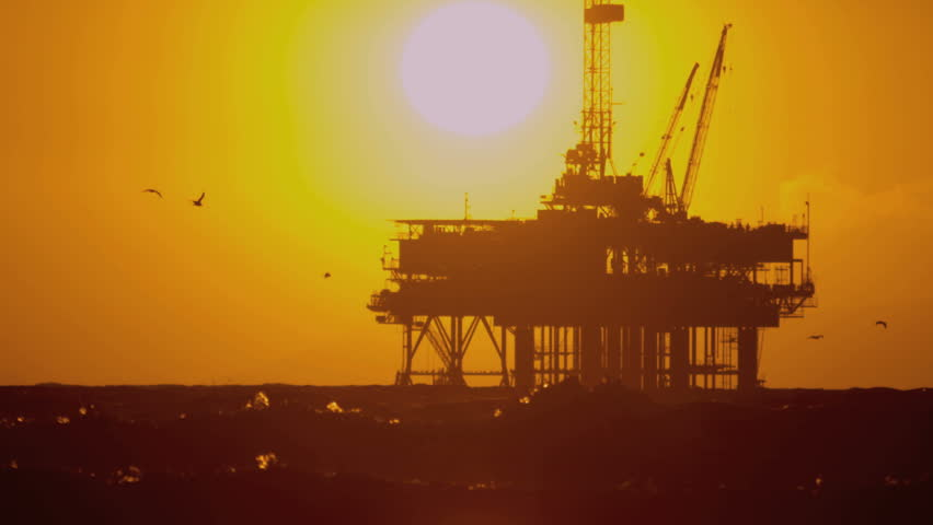 Offshore coastal oil drilling rig producing unrefined fuel sunset silhouette shot on RED EPIC