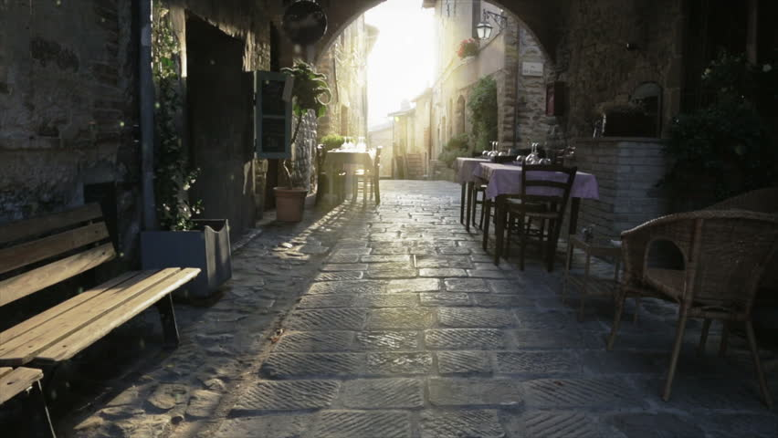 Outdoors restaurant on medieval town at sunset