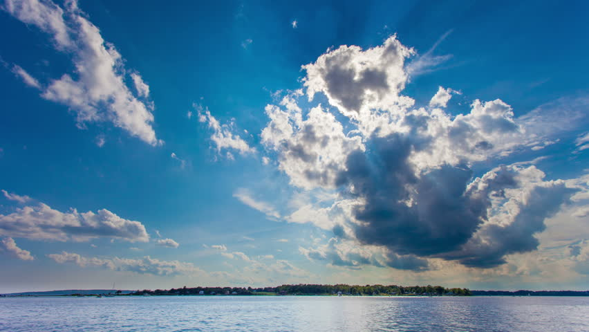 Beautiful time lapse of rays of sunlight breaking through big white clouds over the water.