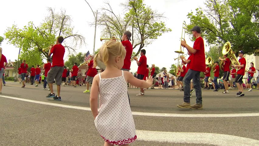 MORONI UTAH JUL 2013: Little girl waves rural small town marching band community annual 4th July parade. Families return to hometown for family fun and recreation. Granddaughter enjoying celebration.