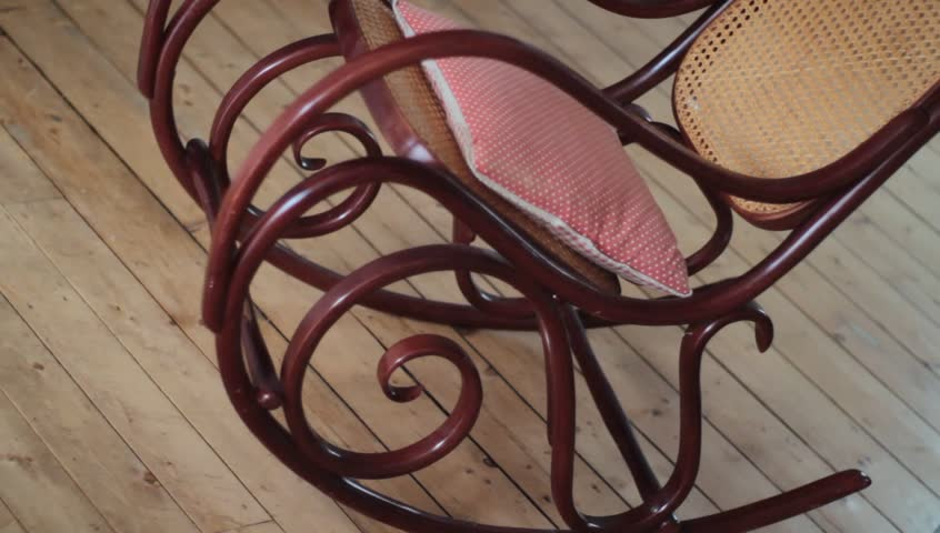 a fine vintage rocking chair is rocking on some wood flooring