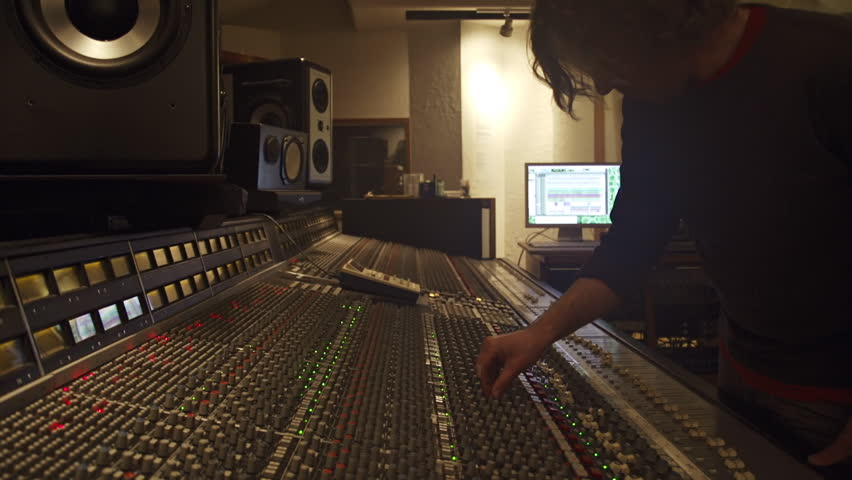 Young audio recording professional adjusts large mixing board in recording