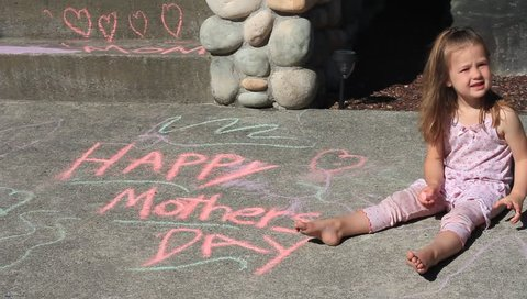 A child writes a mothers day message on the sidewalk with chalk.