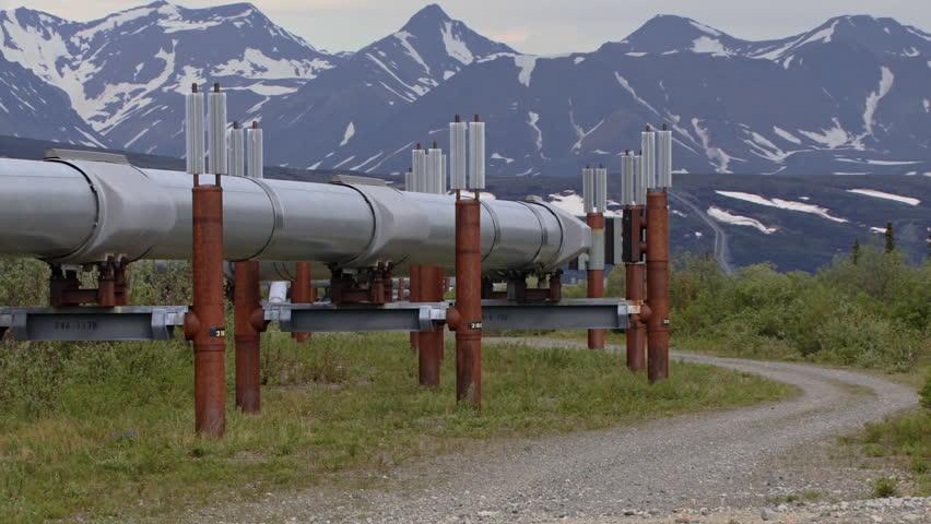 Trans-Alaskan Pipeline snaking up a far-off hill toward distant mountains