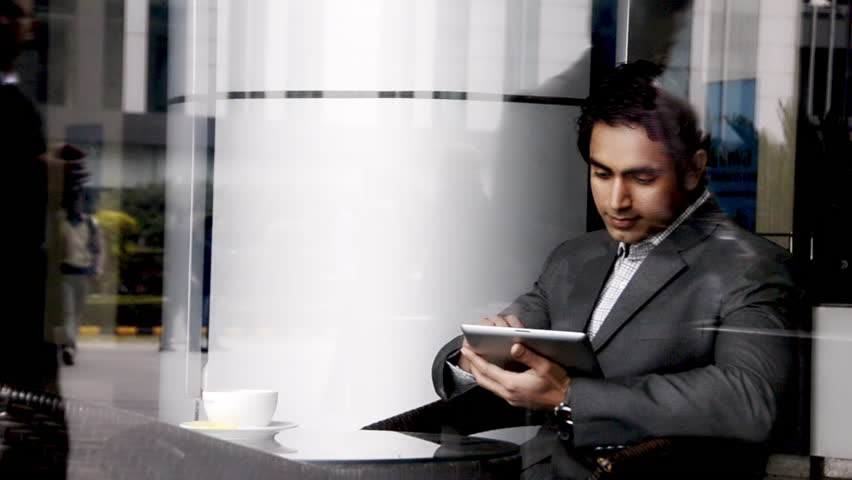Shot of a businessman sitting in an office canteen and using a digital tablet