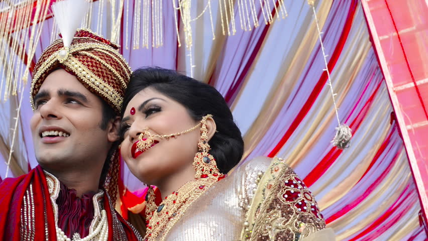 Pan shot of Indian bride and groom in traditional wedding dress posing under a mandap