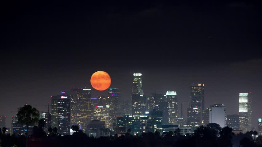 Full moon aka supermoon rising above downtown Los Angeles skyline at night. Timelapse.