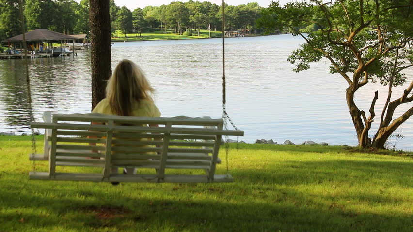 A blonde haired woman enjoys swinging on a wooden swing that over looks a sparkling lake on a summer day