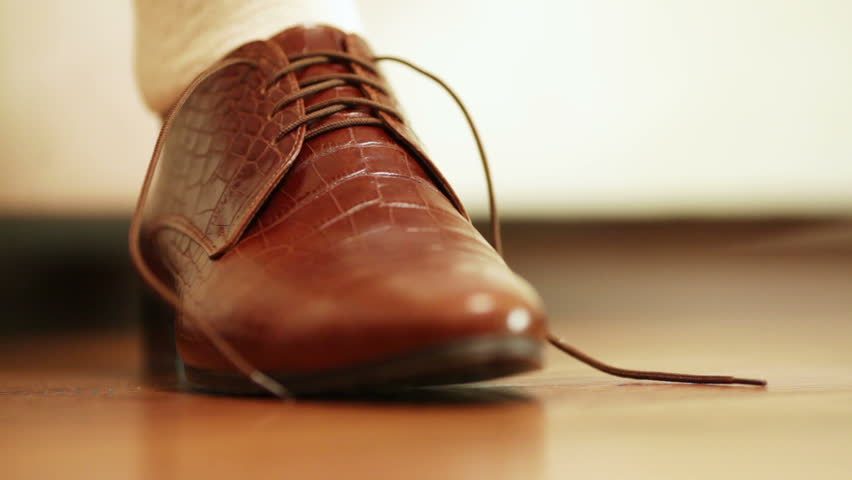 Man tying shoelaces on expensive brown shoes