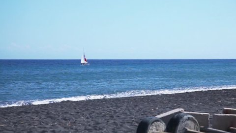 Black sand beaches. Passing yacht. SANTORINI. GREECE