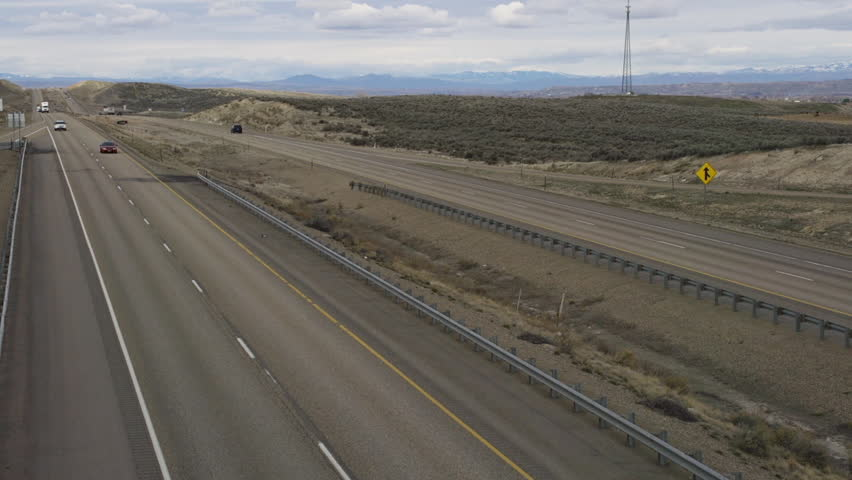 View from a highway overpass of cars and trucks driving southbound on Interstate