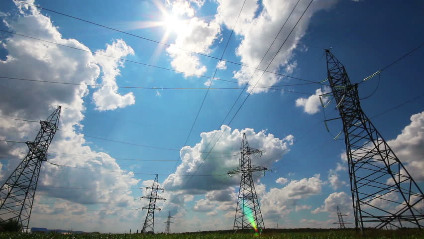 tall electric masts against sun and cloudy sky - timelapse