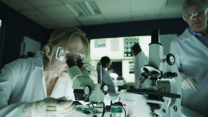 Mature male and female scientists or researchers working together in a dark laboratory, carrying out experiments with chemicals and microscope. In slow motion. | Shutterstock HD Video #4362131