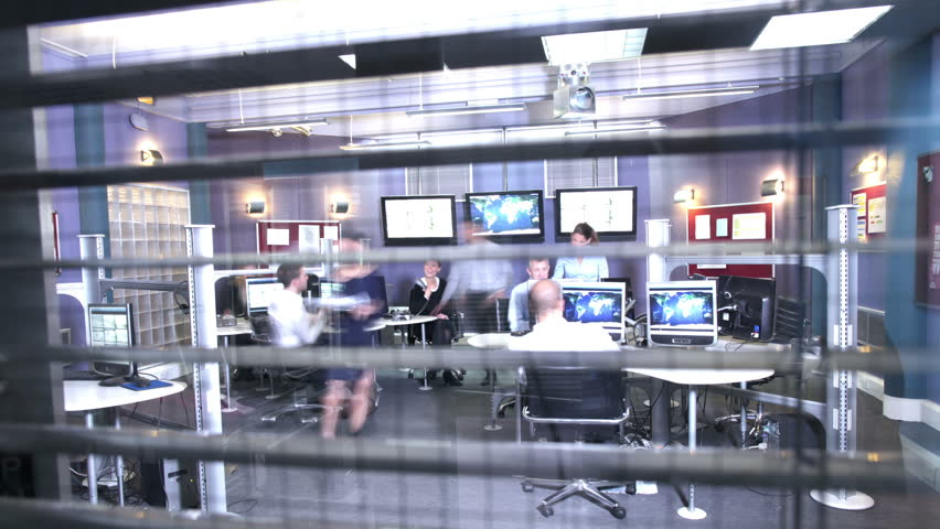 Time lapse of a busy security team watching the screens in a system control center. Could be a weather station or airport traffic control room. Could be a police or government surveillance facility.