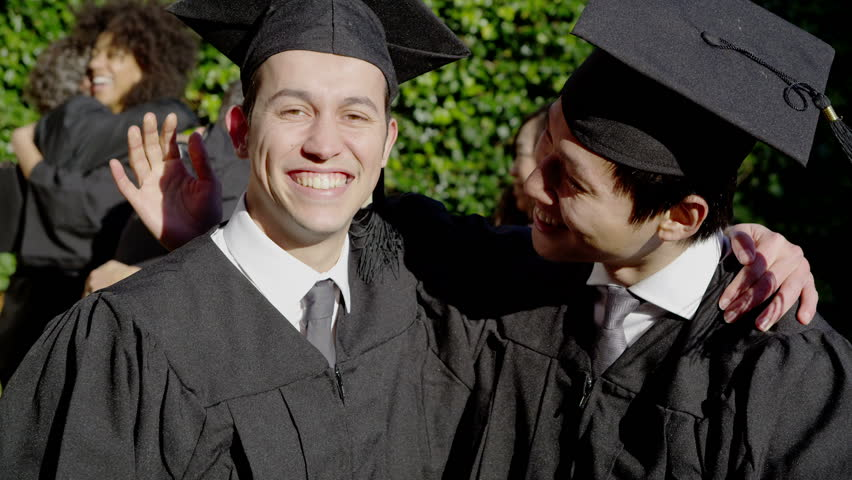 Portrait of 2 happy male graduates on graduation day. They embrace and smile at the camera as their friends and their families celebrate behind them. In slow motion.