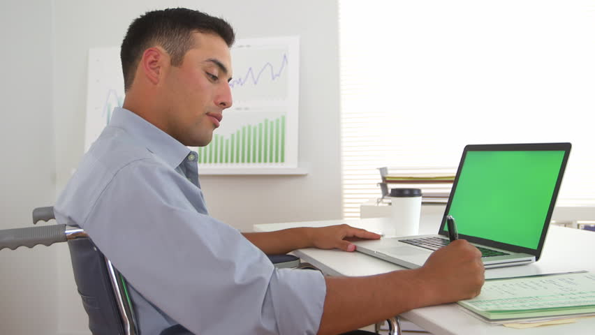 Hispanic business man in wheelchair using laptop with greenscreen