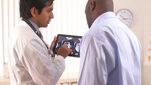 Hispanic doctor using tablet pc to share MRI with patient