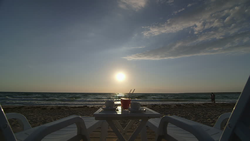 Two lounge chair, table with coffee and drinks on summer beach at sunset. Romantic couple in the background