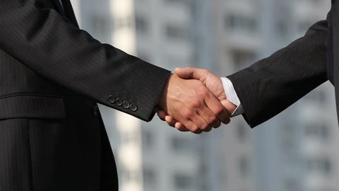 Close-up of business people shaking hands firmly developing business bonds