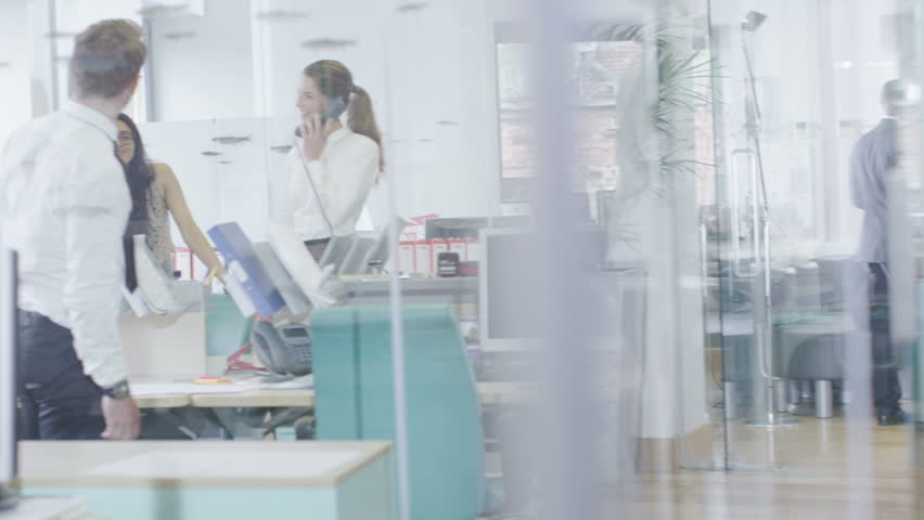 Young creative professionals taking care of business in a light and modern office. In slow motion. | Shutterstock HD Video #4389035
