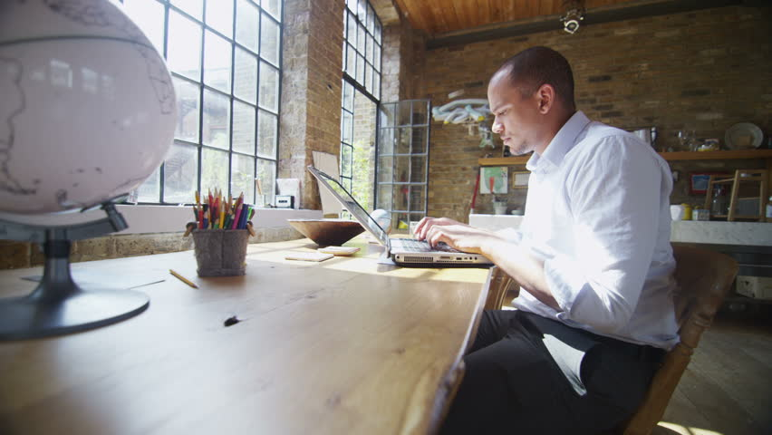 Attractive mixed race professional man working on a laptop computer is alone with his thoughts as he looks out of the window. | Shutterstock HD Video #4394909
